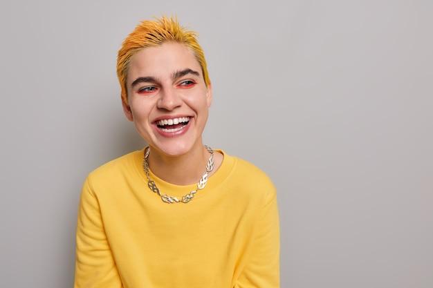 Portrait d'un hipster positif avec une coiffure jaune, un maquillage vif et vif, vêtu d'une chaîne en métal de cavalier décontractée, croit qu'un look extraordinaire pose contre un mur gris, un espace de copie vierge