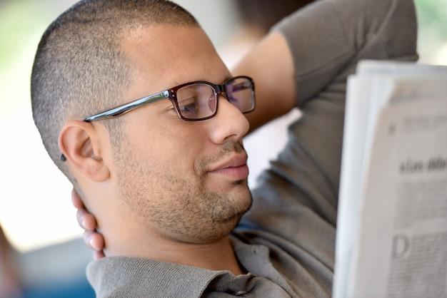Portrait, hispanique, mec, lunettes, journal lisant