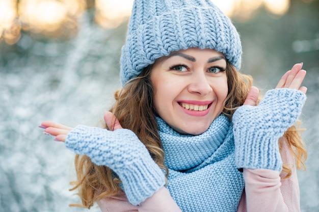 Portrait d'hiver de la belle femme souriante avec des gants bleus de flocons de neige et pull tricoté.