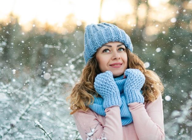 Portrait d'hiver de la belle jeune femme brune bouclée portant une écharpe tricotée bleue couverte de neige.