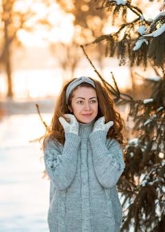 Portrait d'hiver de la belle jeune femme brune bouclée portant un pull tricoté gris recouvert de neige.