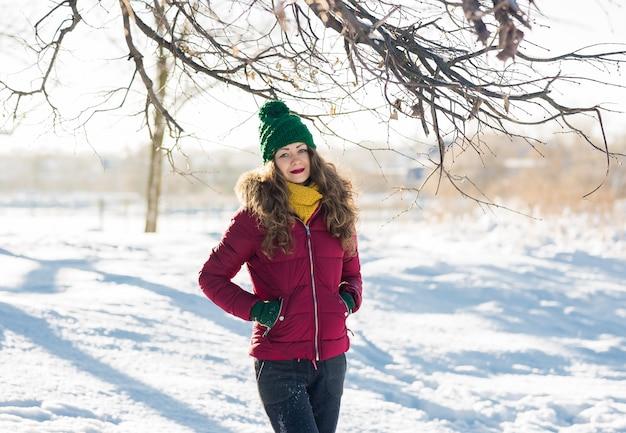 Portrait d'hiver de la belle jeune femme brune portant un snood jaune dans la neige. concept de mode beauté hiver neige.