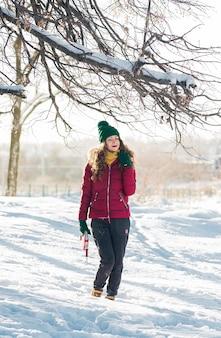 Portrait d'hiver de la belle jeune femme brune portant un snood jaune dans la neige