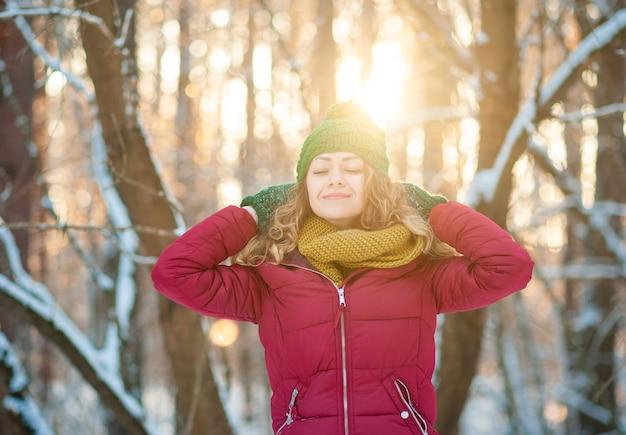 Portrait d'hiver de la belle jeune femme brune portant un snood jaune dans la neige.