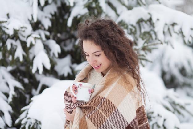 Portrait d'hiver de la belle jeune femme brune portant le snood tricoté couvert de neige