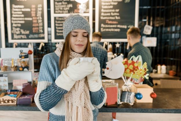 Portrait d'hiver de la belle jeune femme en écharpe tricotée, bonnet tricoté, mitaines, pull chaud avec une tasse de café.
