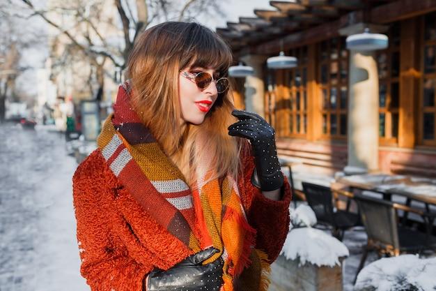 Portrait d'hiver d'élégante femme brune à lunettes rétro posant en plein air