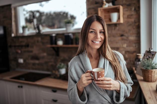 Portrait d'hiver d'une femme brune buvant du café du matin.