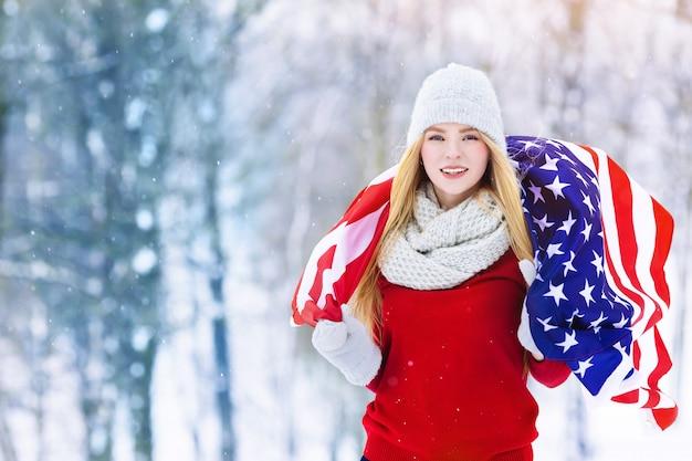 Portrait d'hiver de la jeune adolescente avec le drapeau des etats-unis. beauty joyful model girl rire et s'amuser à winter park
