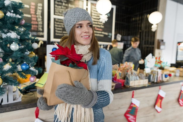 Portrait d'hiver de jeune femme avec une fleur de poinsettia rouge de noël