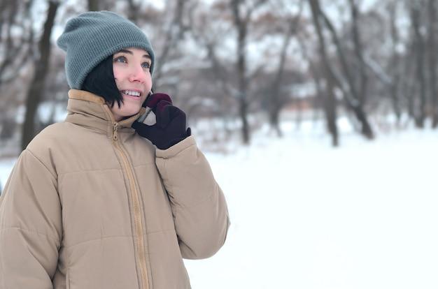 Portrait d'hiver de jeune fille avec smartphone