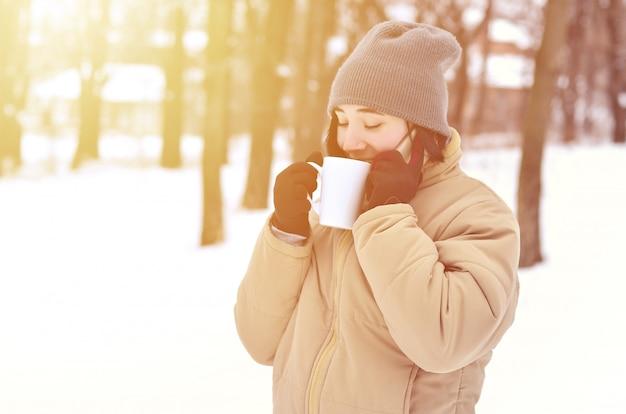 Portrait d'hiver de jeune fille avec une tasse de café et smartphone