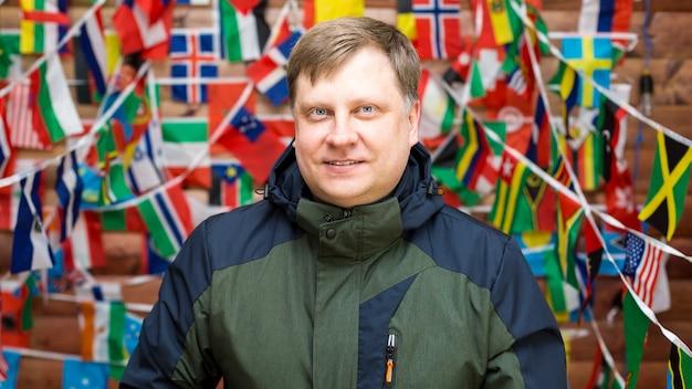 Portrait d'un homme de 40 à 45 ans en tenue décontractée sur fond de mur avec un drapeau.