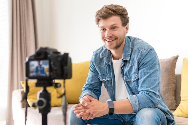 Portrait d'un homme adulte enregistrant pour un blog personnel à la maison