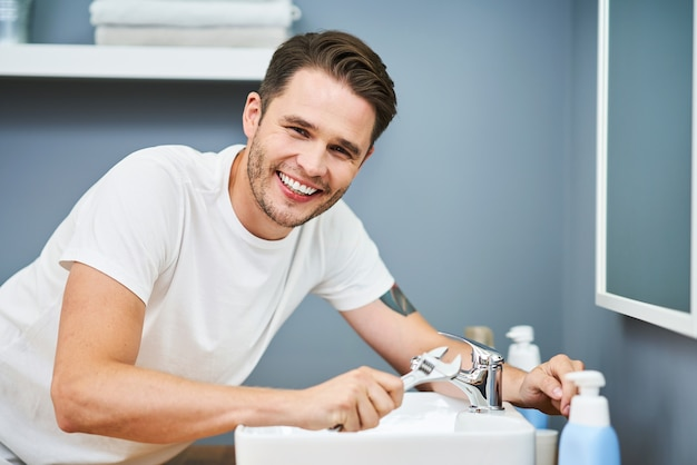 Portrait d'un homme adulte fixant un lavabo dans la salle de bain