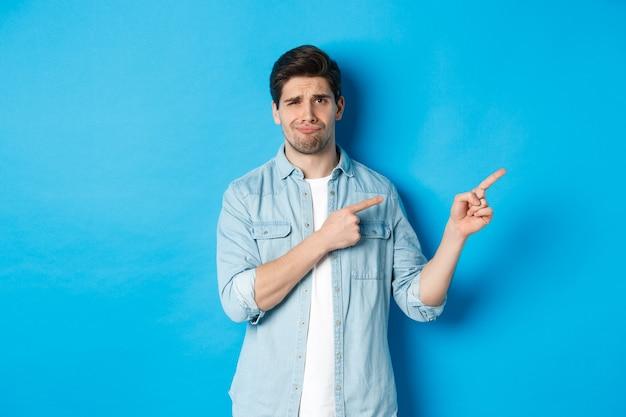 Portrait d'un homme adulte sceptique pointant du doigt vers la droite et souriant, exprime la déception et le doute, debout sur fond bleu