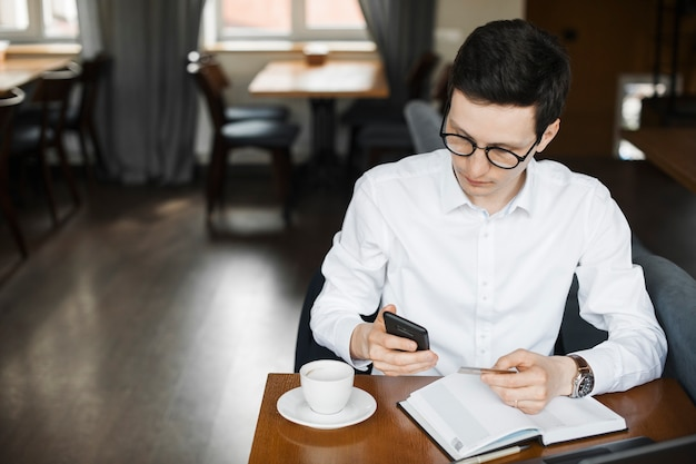 Portrait d'homme d'affaires adulte élégant confiant fonctionnant avec son smartphone tout en utilisant une carte de crédit holding assis dans un café travaillant à son ordinateur portable.