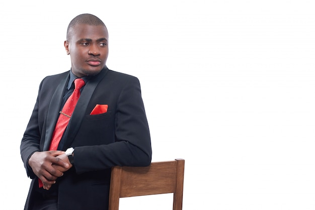 Portrait d'homme d'affaires africain posant sérieusement et regardant ailleurs, s'appuyant sur une chaise et se tenant la main ensemble.