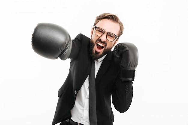 Portrait d'homme d'affaires agressif en costume noir et lunettes crier tout en frappant dans des gants de boxe, isolé sur mur blanc