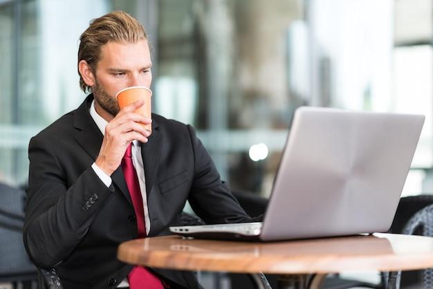 Portrait d'un homme d'affaires à l'aide de son ordinateur portable dans un café