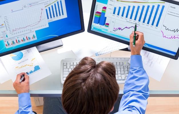 Portrait d'un homme d'affaires analysant des tableaux et des graphiques sur des écrans d'ordinateur, vue de dessus