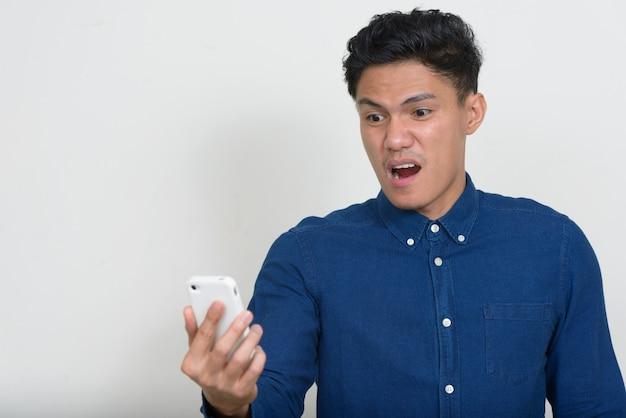 Portrait d'homme d'affaires asiatique à l'aide de téléphone et à la choqué