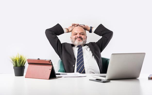 Portrait d'un homme d'affaires asiatique indien senior satisfait assis sur son lieu de travail devant l'ordinateur et regardant la caméra tout en se relaxant. vieux pieds d'homme professionnel sur le bureau
