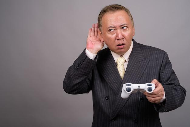 Portrait d'homme d'affaires asiatique mature contre mur gris