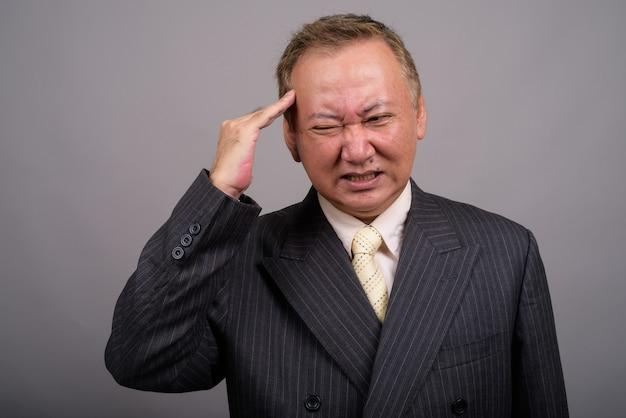 Portrait d'homme d'affaires asiatique mature sur fond gris
