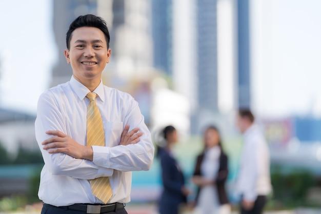 Portrait d'homme d'affaires asiatique prospère debout avec les bras croisés debout devant les immeubles de bureaux modernes
