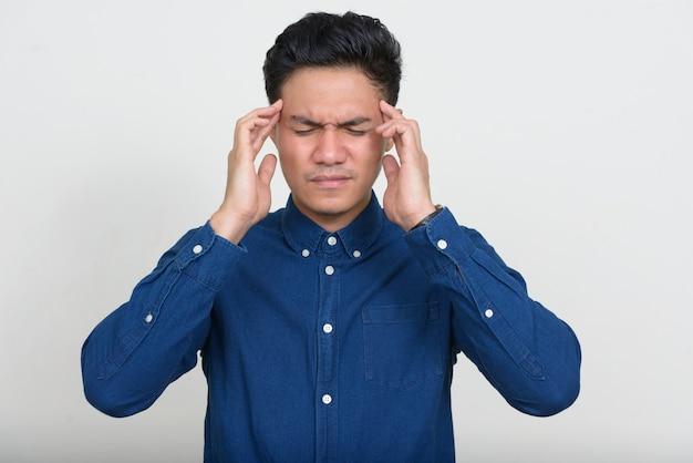 Portrait d'homme d'affaires asiatique stressé ayant des maux de tête