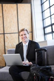 Portrait d'homme d'affaires assis sur un canapé et utilisant un ordinateur portable au bureau