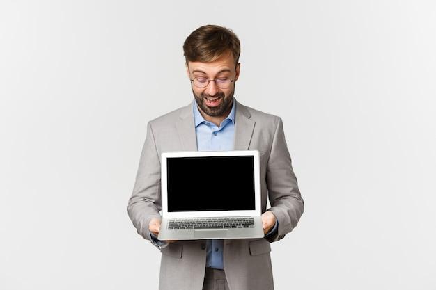 Portrait d'homme d'affaires barbu et lunettes, montrant et regardant l'écran du portable