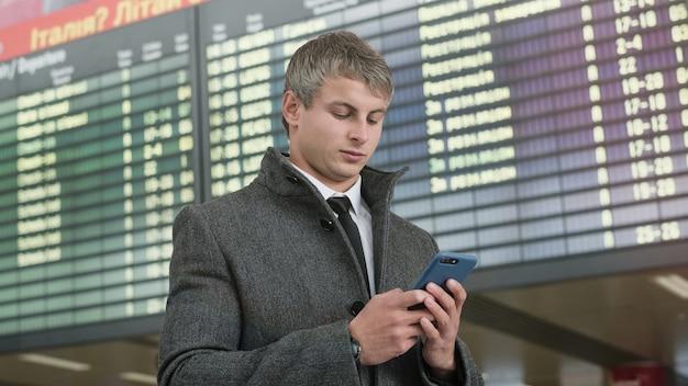 Portrait d'un homme d'affaires beau à l'aide de smartphone.