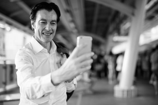 Portrait d'homme d'affaires beau mature à la découverte de la ville en noir et blanc