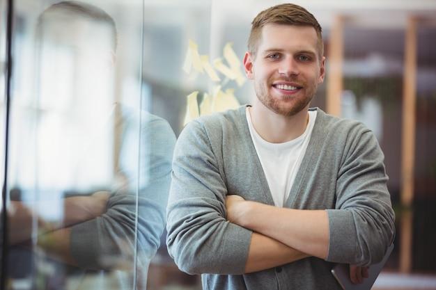 Portrait, homme affaires, bras, traversé, bureau