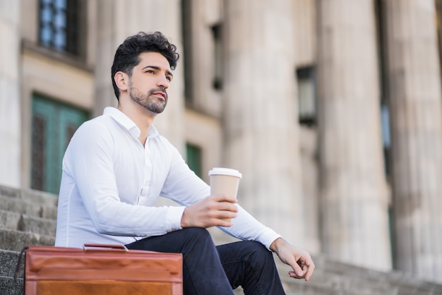 Portrait d'un homme d'affaires buvant une tasse de café sur une pause du travail alors qu'il était assis dans les escaliers à l'extérieur