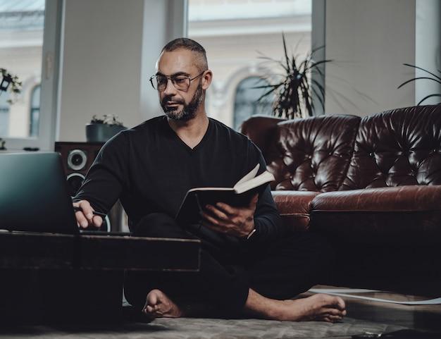 Portrait d'un homme d'affaires caucasien avec des lunettes dans des vêtements domestiques noirs à l'aide de son ordinateur portable tenant un ordinateur portable dans le salon.