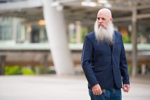 Portrait d'homme d'affaires chauve mature avec une longue barbe dans les rues de la ville à l'extérieur