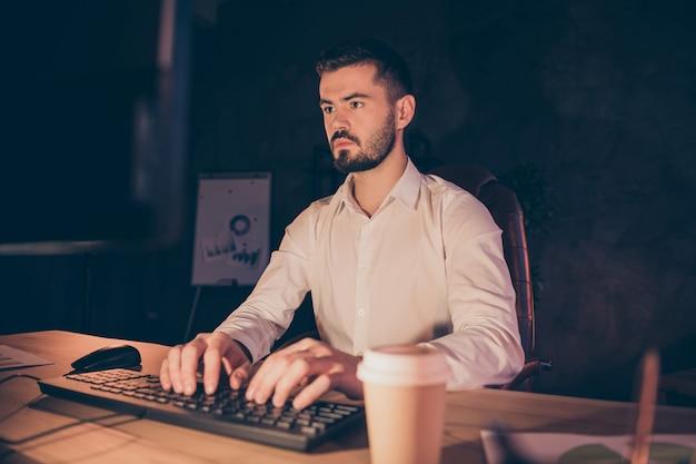 Portrait d'homme d'affaires concentré rester la nuit dans un bureau sombre travaillant sur ordinateur