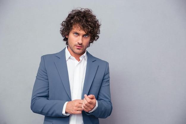 Portrait d'un homme d'affaires confiant à l'avant sur un mur gris