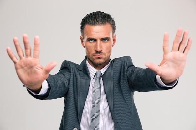 Portrait d'un homme d'affaires confiant montrant un geste d'arrêt avec des paumes isolées
