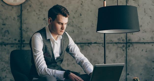 Portrait d'un homme d'affaires confiant travaillant à l'ordinateur portable dans son bureau contre un mur gris au sérieux.