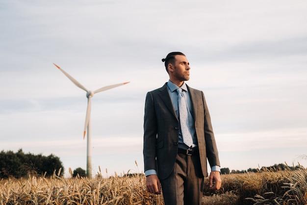 Portrait d'un homme d'affaires en costume gris sur un champ de blé dans la perspective d'un moulin à vent et du ciel du soir