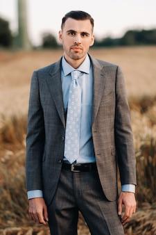 Portrait d'un homme d'affaires en costume gris dans un champ de blé. un homme dans la nature en veste et cravate