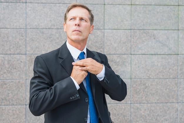 Portrait, homme affaires, debout, devant, mur carrelé