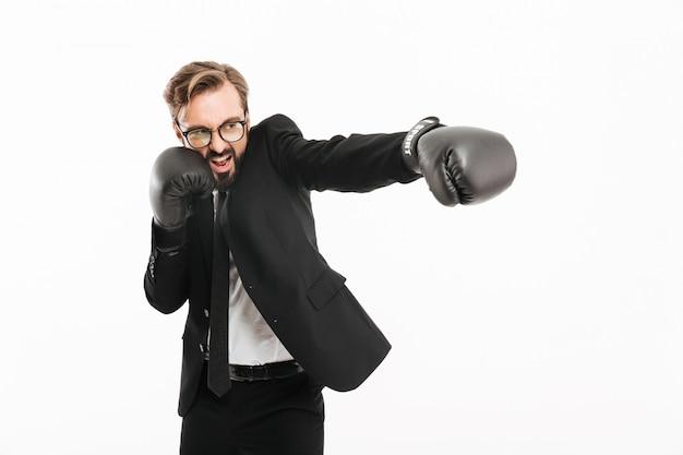 Portrait d'homme d'affaires décisif en costume noir et lunettes poinçonnage emoionally côté dans des gants de boxe, isolé sur mur blanc