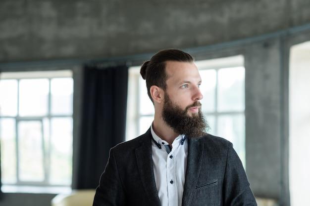 Portrait d'homme d'affaires. élégant beau mâle barbu dans un espace de bureau moderne.