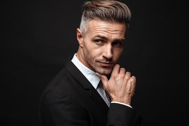 Portrait d'homme d'affaires européen mal rasé vêtu d'un costume formel posant à la caméra et regardant de côté isolé sur un mur noir