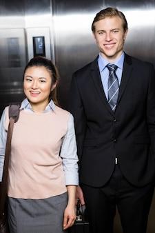 Portrait, homme affaires, femme affaires, debout, ascenseur, bureau